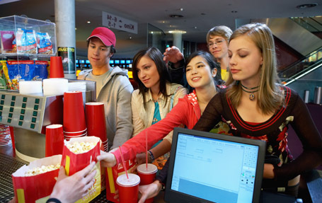 Group of teenagers (14-17) buying refreshments in cinema, smiling
